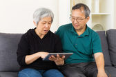 Senior couple using tablet at home — Foto Stock