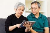 使用平板电脑对亚裔夫妇 — 图库照片