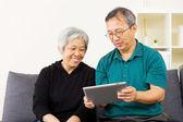 Pareja asiática mirando juntos tablet — Foto de Stock