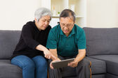 Senior couple watching on tablet at home — Stok fotoğraf