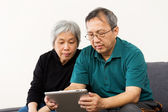 Asian old couple reading on tablet — Foto Stock