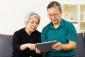 Asian couple using tablet together at home — Stock Photo