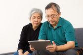 Asia couple using tablet at home — Stock Photo