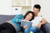 亚洲孕妇和她的丈夫在家里使用平板电脑 — 图库照片