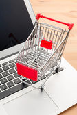 Shopping trolley with laptop — Stock Photo
