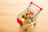 Trolley with golden coin — Stock Photo