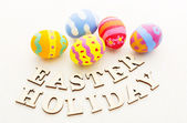 Colourful patterm easter eggs with wooden letters — Stock Photo
