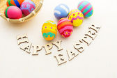 Painted easter eggs in basket with wooden text — Foto Stock