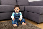 Little boy sitting on carpet — Stock Photo