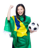 Asian female soccer fan with ball and flag — Stock Photo