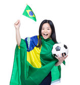 Asian female soccer fan with ball and flag — Zdjęcie stockowe