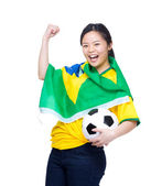 Excited asian woman draped with Brazil flag and holding soccer ball — Stock Photo