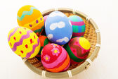Colourful easter eggs in wicker basket — Stock Photo