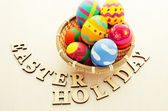 Easter eggs in basket with wooden text — Stockfoto