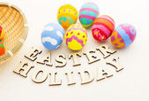 Painted easter eggs in basket with wooden text — Stockfoto