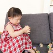 Asian baby girl play toy blocks and sitting on sofa — Stock Photo