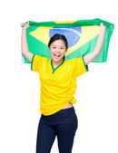 Asian female soccer fans holding Brazil flag — Stock Photo