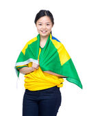 Asian female soccer fans draped with Brazil flag — Stock Photo