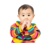 Baby girl put toy block into mouth — Foto Stock