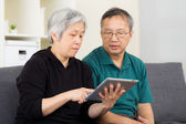 Asian old couple using tablet — Stock Photo