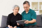 Senior couple using their tablet — Stock Photo