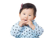 Asia baby girl eating candy — Stock Photo