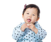 Asia baby girl suck toy block into mouth — Stock Photo
