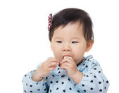 Asian baby girl suck toy block into mouth — Stock Photo