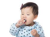 Asian baby girl eating snack — Stock Photo