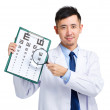 Male doctor holding optometry chart and magnifying glass — Stock Photo #46853283