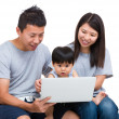 Mother, father and baby son looking at laptop computer — Stock Photo