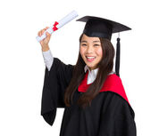 Happy graduate student girl in an academic gown with diploma — Stock Photo