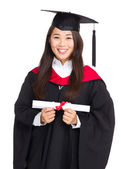 Young graduate girl student holding and showing diploma — ストック写真