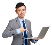 Businessman holding laptop and finger pointing to screen — 图库照片