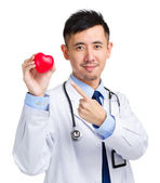 Medical doctor holding heart squeezing ball — Stock Photo