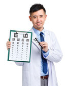 Male oculist holding eye chart and glasses — Stock Photo