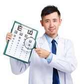 Male doctor holding optometry chart and magnifying glass — Stock Photo