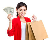 Woman holding cash and shopping bag — 图库照片