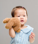 Baby girl holding her bear doll — Stock Photo