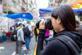Female tourist taking photo with camera in street at Hong Kong — Stockfoto