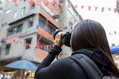 Woman taking photo using camera — Stockfoto