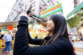 Woman taking selfise in street market — Stockfoto