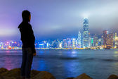 Girl viewing Hong Kong skyline at night — Stockfoto