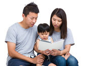 Asian parent reading book with baby son — Stockfoto