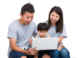 Mother, father and baby son looking at laptop computer — Stockfoto