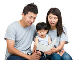 Young couple reading book with baby boy — Stock fotografie