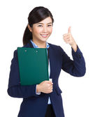 Businesswoman holding clipboard showing thumb up — Stockfoto