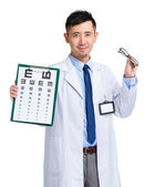 Asian oculist holding eye chart and glasses — Stock Photo