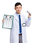 Asian oculist holding eye chart and glasses — Stock Photo