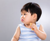 Little boy eat biscuit and look aside — Stock Photo